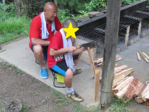 薪割りをする職員と児童の写真