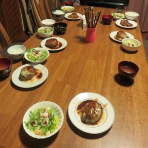 食卓にハンバーグやサラダが並んでいる写真